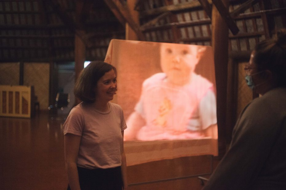 Clare speaking with a friend in front of a projection of herself as a baby