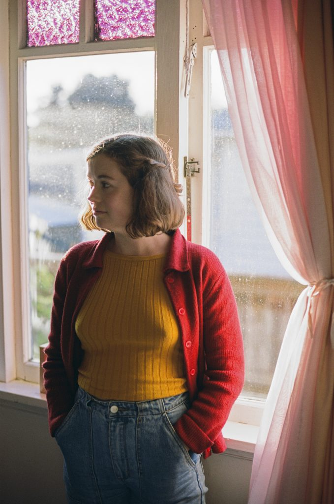 Clare in yellow standing beside a window