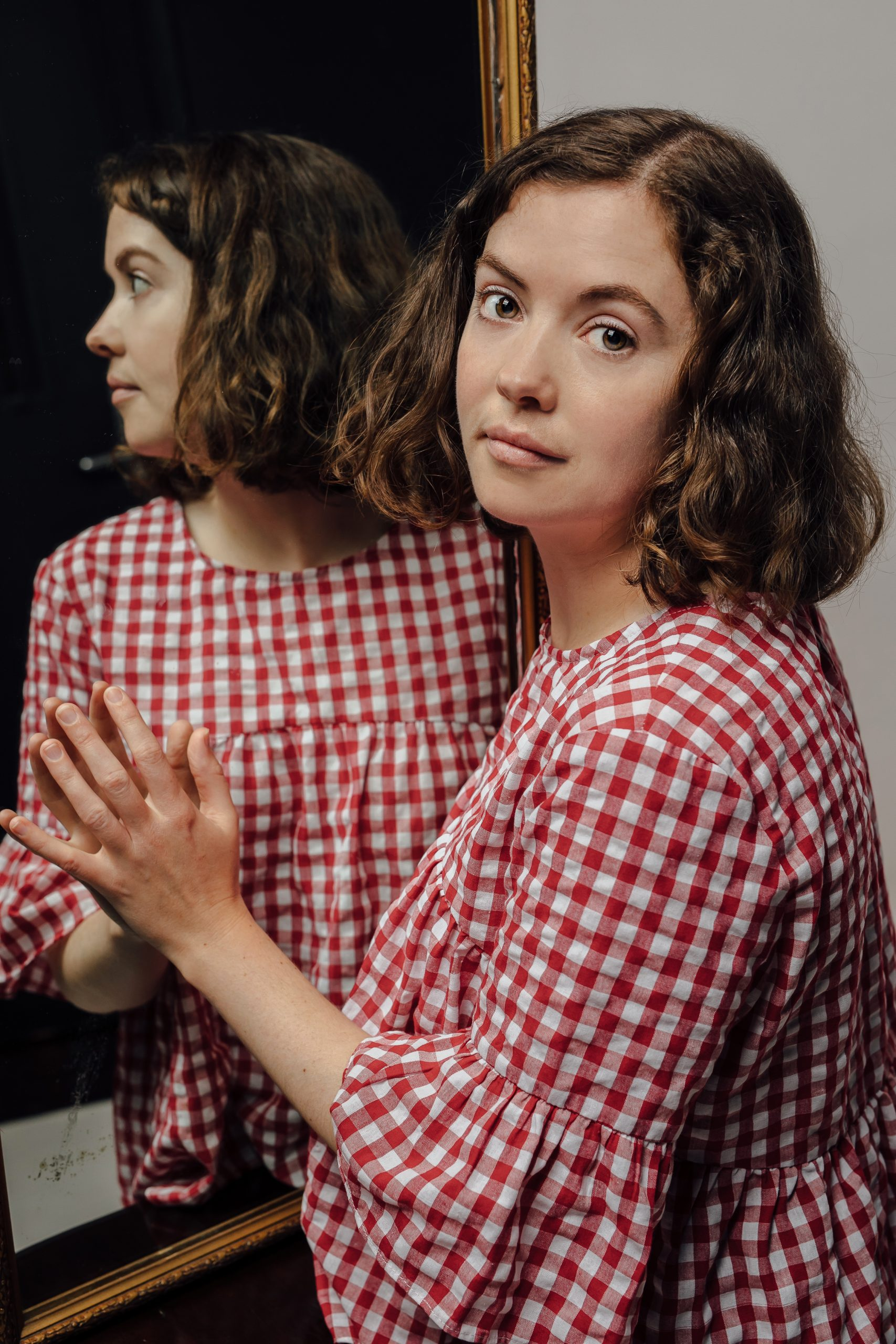 Clare as an adult reflected in a mirror wearing a red and white gingham top