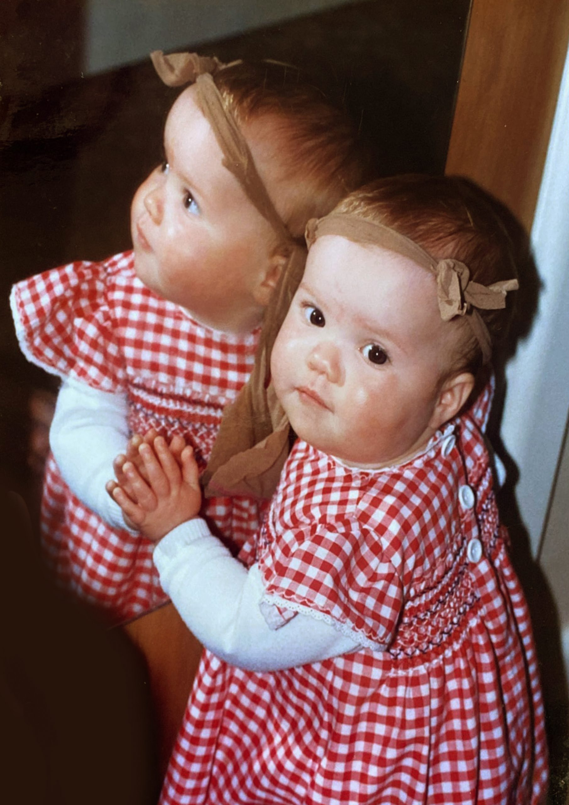 Clare as a baby reflected in a mirror wearing a red and white gingham top