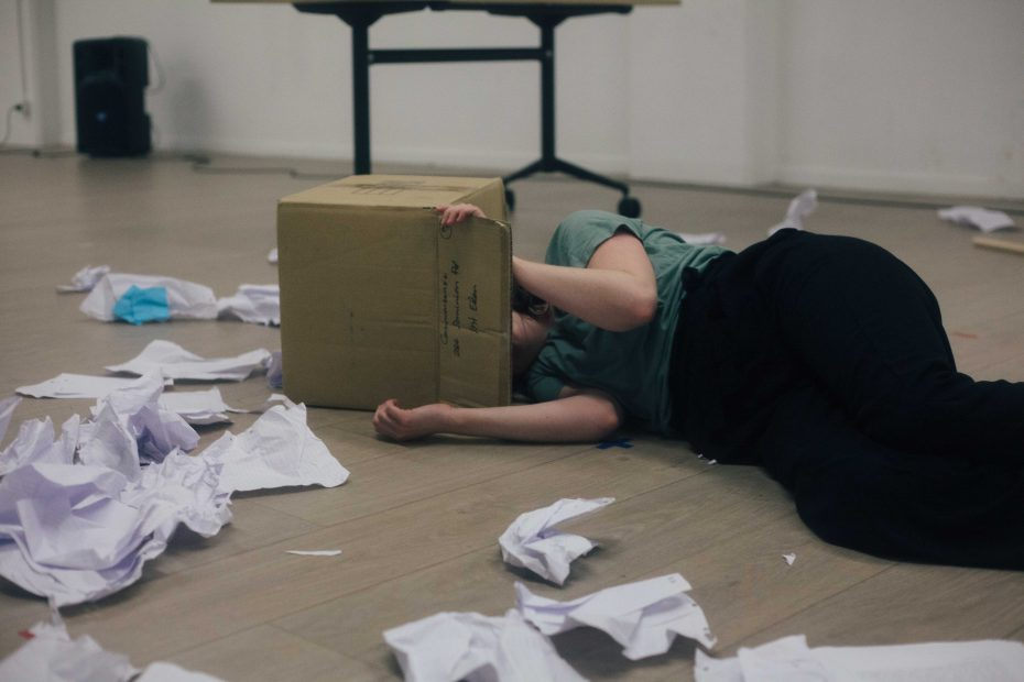 Clare lying down with her head in a cardboard box, papers strewn on the ground