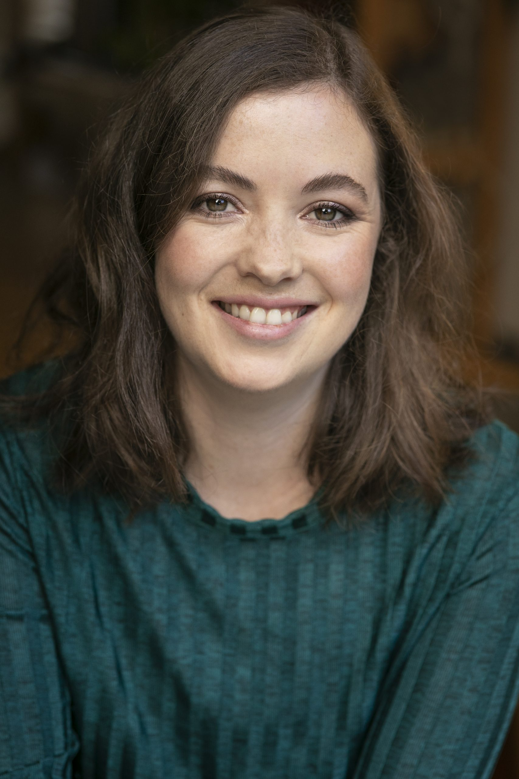 Photo of brunette Clare Marcie in a teal long sleeved top smiling warmly